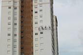 Trabalhadores pintam prédio