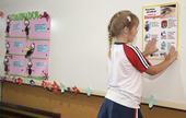 Criança cola cartaz em escola