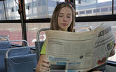 Person reads newspaper in public place