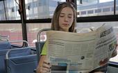 Pessoa lê jornal em local público